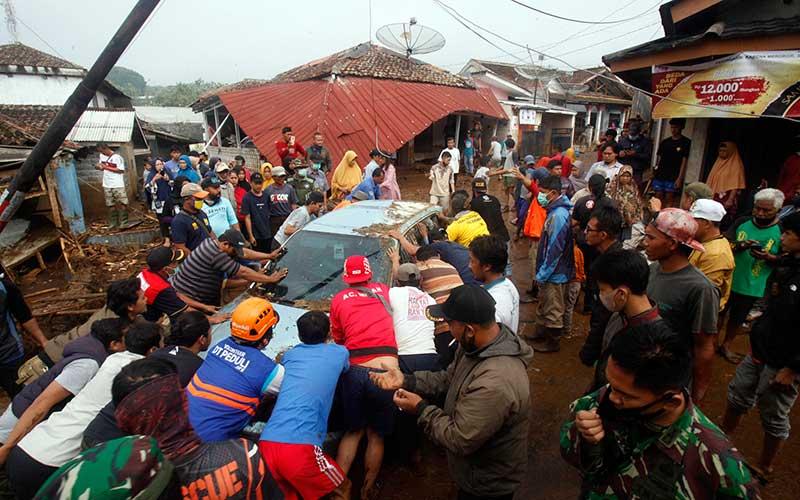 Sejumlah warga mengevakuasi mobil yang terbawa arus pasca  banjir bandang di  Kampung Cibuntu, Desa Pasawahan, Kecamatan Cicurug, Sukabumi, Jawa Barat, Selasa (22/9/2020). Data sementara yang dikeluarkan Badan Penanggulangan Bencana Daerah Kabupaten Sukabumi, Jawa Barat, dampak akibat banjir bandang yang terjadi di Kecamatan Cicurug, Senin (21/9), mengakibatkan 12 rumah hanyut dan 85 rumah terendam. ANTARA FOTO/Yulius Satria Wijaya