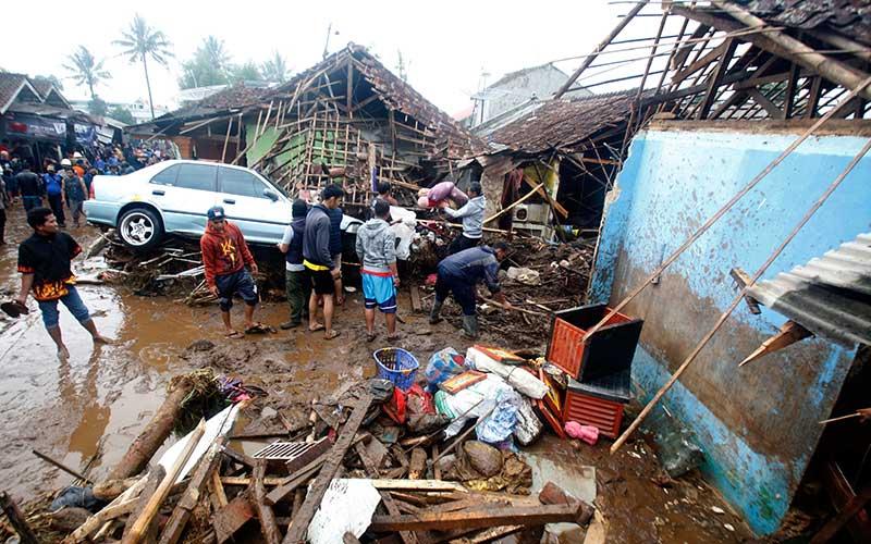Warga meihat mobil yang rusak terbawa arus banjir bandang di  Kampung Cibuntu, Desa Pasawahan, Kecamatan Cicurug, Sukabumi, Jawa Barat, Selasa (22/9/2020). Data sementara yang dikeluarkan Badan Penanggulangan Bencana Daerah Kabupaten Sukabumi, Jawa Barat, dampak akibat banjir bandang yang terjadi di Kecamatan Cicurug, Senin (21/9), mengakibatkan 12 rumah hanyut dan 85 rumah terendam. ANTARA FOTO/Yulius Satria Wijaya