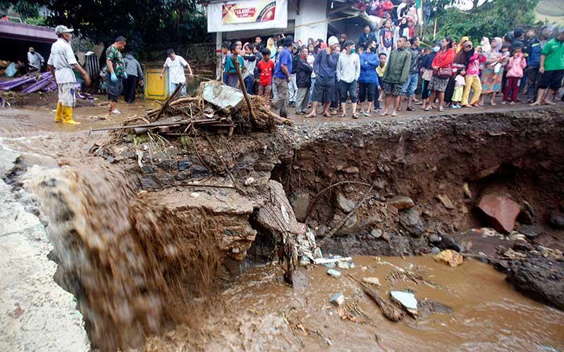 Warga melihat jalanan yang rusak pasca  banjir bandang di  Kampung Cibuntu, Desa Pasawahan, Kecamatan Cicurug, Sukabumi, Jawa Barat, Selasa (22/9/2020). Data sementara yang dikeluarkan Badan Penanggulangan Bencana Daerah Kabupaten Sukabumi, Jawa Barat, dampak akibat banjir bandang yang terjadi di Kecamatan Cicurug, Senin (21/9), mengakibatkan 12 rumah hanyut dan 85 rumah terendam. ANTARA FOTO/Yulius Satria Wijaya