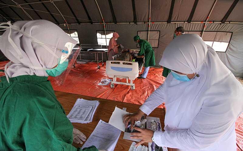 Petugas medis melakukan screening pasien ditenda darurat di depan IGD RSU Cut Meutia Aceh Utara, Aceh, Selasa (22/9/2020). Screening bagi pasien yang berobat ke rumah sakit tersebut dilakukan untuk penyaringan pasien sebelum masuk IGD, mengantisipasi penularan Covid-19 dari pasien kepada para tenaga Kesehatan, menyusul semakin meningkatnya kasus Covid-19 di Aceh.  ANTARA FOTO/Rahmad
