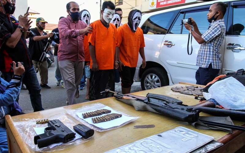 Polisi Satuan Reserse Kriminal menghadirkan Empat tersangka penculikan bersama barang bukti senjata api, di Polres Lhokseumawe, Aceh, Selasa (22/9/2020). Ke Empat tersangka jaringan Kelompok Kriminal Bersenjata (KKB) itu yakni MJ, IS (28), AU (40), dan JN (34) melakukan penculikan terhadap Maimun Darwis (44) pemilik Showroom sepeda motor di Lhokseumawe, ditangan tersangka polisi mengamankan 1 pucuk AK-56, 24 butir peluru dan 1 pucuk pistol Sig Sauer berikut 5 butir peluru. ANTARA FOTO/Rahmad