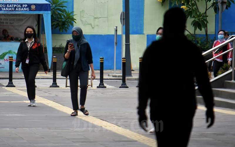 Pekerja melintas saat jam pulang kerja di Jakarta, Rabu (23/9/2020). Pemerintah memproyeksikan tingkat pengangguran terbuka dan kemiskinan di Indonesia akan melonjak tinggi akibat dari pandemi Covid-19 pada akhir 2020. Bisnis/Abdurachman