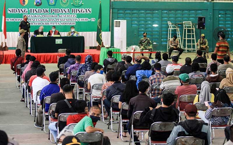 Warga pelanggar protokol kesehatan mengikuti sidang tindak pidana ringan di GOR Tennis Indoor Sidoarjo, Jawa Timur, Kamis (24/9/2020). Sidang tindak pidana ringan (tipiring) dengan sanksi denda sebesar Rp150 ribu tersebut dilakukan untuk menerapkan disiplin dan penegakan hukum terhadap pelanggar protokol kesehatan dalam upaya pencegahan penyebaran Covid-19. ANTARA FOTO/Umarul Faruq