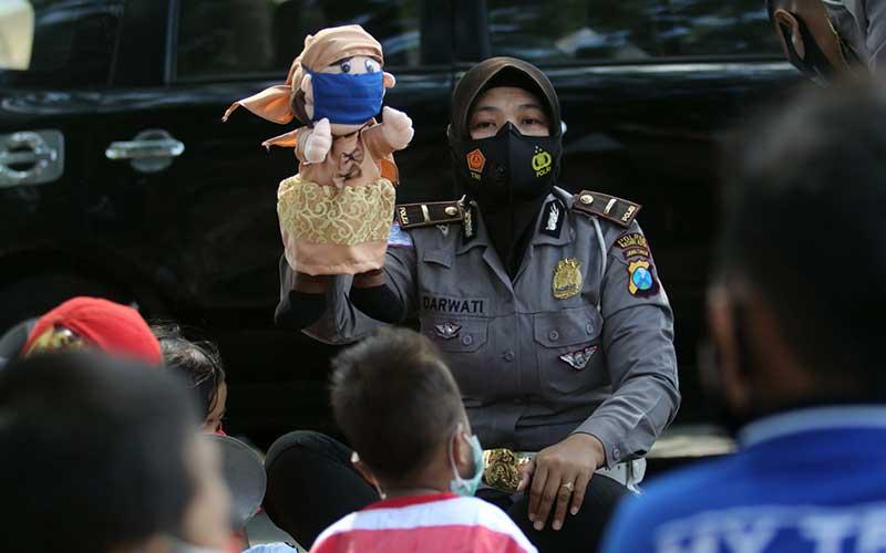 Polwan memainkan boneka bermasker di hadapan anak-anak di kawasan rumah susun Kelurahan Dandangan, Kota Kediri, Jawa Timur, Kamis (24/9/2020). Pentas boneka oleh kepolisian daerah setempat tersebut sebagai sarana edukasi penerapan protokol kesehatan kepada anak-anak agar terhindar dari penularan Covid-19. ANTARA FOTO/Prasetia Fauzani