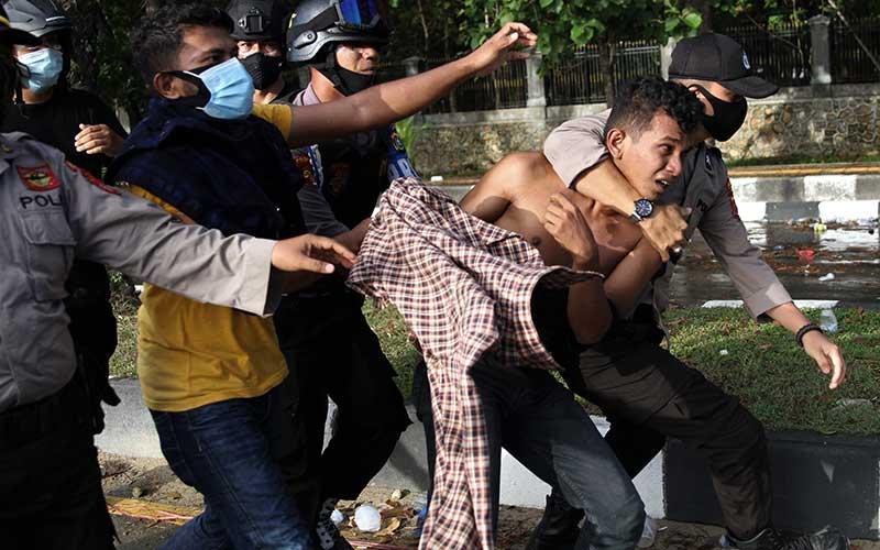 Aparat Kepolisian mengamankan seorang mahasiswa yang anarkis saat unjuk rasa mahasiswa menuntut penuntasan kasus kematian dua rekannya di depan Markas Polda Sulawesi Tenggara, Kendari, Sulawesi Tenggara, Sabtu (26/9/2020). Mahasiswa meminta kepada kepolisian untuk mengusut dan menuntaskan kasus kematian Randi dan Muhammad Yusuf Kardawi yang meninggal dunia diduga ditembak saat aksi penolakan RKUHP dan RUU Kontroversial pada 26 September 2019 lalu. ANTARA FOTO/Jojon