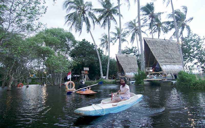 Wisatawan bermain kano di Pantai Cacalan, Banyuwangi, Jawa Timur, Sabtu (26/9/2020). Tempat wisata alam menjadi lokasi pilihan warga untuk berlibur pada masa pandemi Covid-19 sebagai cara untuk menghindari keramaian. ANTARA FOTO/Budi Candra Setya