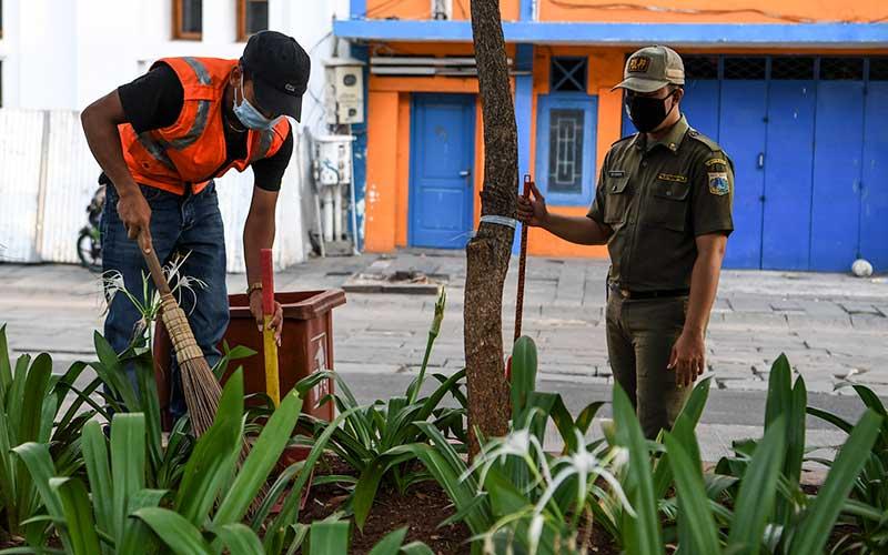 Warga yang melanggar aturan pemberlakuan Pembatasan Sosial Berskala Besar (PSBB) dihukum menyapu usai terjaring Operasi Tertib Masker di kawasan Kota Tua, Jakarta, Minggu (27/9/2020). Berdasarkan data Litbang Satpol PP DKI Jakarta sejak Senin (14/9) tercatat sebanyak 19.361 warga menerima sanksi sosial dan 1.449 warga membayar denda dengan total Rp229.575.000 karena melanggar aturan PSBB tidak mengenakan masker. ANTARA FOTO/Hafidz Mubarak A