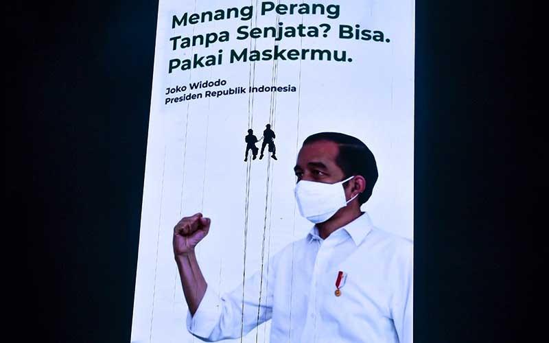 Pekerja membersihkan layar iklan pesan layanan masyarakat terkait penanganan Covid-19 di Jakarta, Minggu (27/9/2020). Presiden Joko Widodo menyampaikan bahwa penanganan pandemi Covid-19 membutuhkan kedisiplinan dan kerja keras dari seluruh komponen bangsa. ANTARA FOTO/Muhammad Adimaja