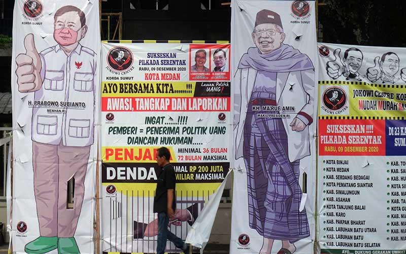 Warga melintas di dekat spanduk berisi ajakan untuk menolak politik uang di Medan, Sumatera Utara, Senin (28/9/2020). Poster yang dibuat oleh Jokowi Centre Korda Sumut tersebut mengajak masyarakat untuk bersama melawan politik uang pada pelaksanaan Pilkada serentak Tahun 2020. ANTARA FOTO/Irsan Mulyadi