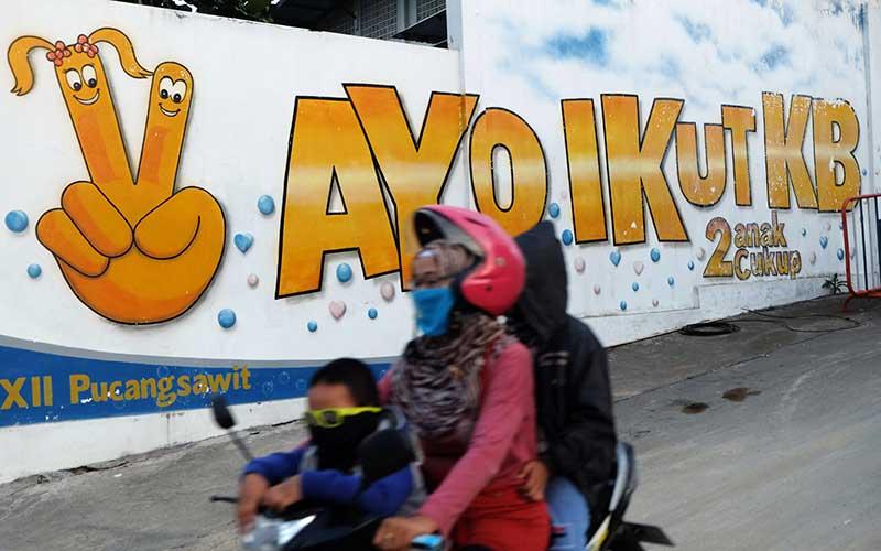 Warga melewati mural bertem Keluarga Berencana di Kampung Pucang Sawit, Solo Jawa Tengah, Senin (28/9/2020). Badan Kependudukan dan Keluarga Berencana Nasional (BKKBN) menargetkan pemberian layanan kontrasepsi jangka panjang terhadap 250 ribu ekseptor Keluarga Berencana (KB) di Indonesia, guna memaksimalkan pelayanan kontrasepsi yang sempat terhenti pada masa awal pandemi Covid-19. ANTARA FOTO/Maulana Surya