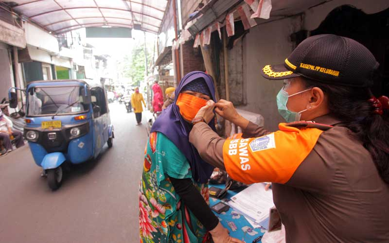 Petugas memakaikan masker kepada warga yang melanggar protokol kesehatan  di kawasan Jalan Menteng Atas, Jakarta, Selasa (29/9/2020). Razia gabungan tersebut untuk meningkatkan kesadaran masyarakat agar mematuhi protokol kesehatan di tengah meningkatnya angka konfirmasi positif Covid-19 di Jakarta. ANTARA FOTO/ Reno Esnir