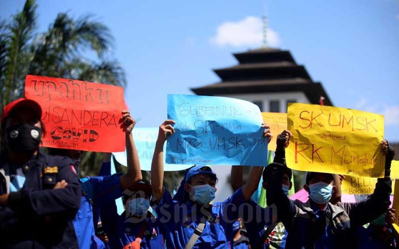 Massa buruh dari berbagai elemen melakukan aksi unjuk rasa di depan Gedung Sate, Bandung, Jawa Barat, Selasa (29/9/2020). Dalam aksinya massa buruh menuntut Gubernur Jawa Barat Ridwan Kamil untuk menandatangani Surat Keputusan (SK) terkait Upah Minimum Sektoral Kabupaten Kota (UMSK) tahun 2020. Bisnis/Rachman