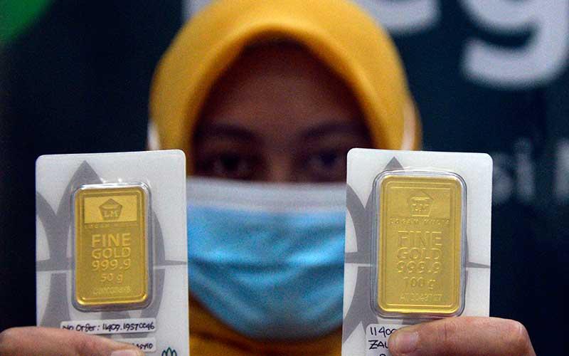 Seorang karyawan menunjukkan kepingan emas di kantor Pegadaian Makassar, Sulawesi Selatan, Kamis (15/10/2020). Harga emas batangan PT Aneka Tambang (Persero) Tbk pada Oktober berada di angka Rp.1.017.000 per gram atau naik Rp.8.000 jika dibandingkan dengan harga emas pada September dengan harga Rp.1.009.000. ANTARA FOTO/Abriawan Abhe