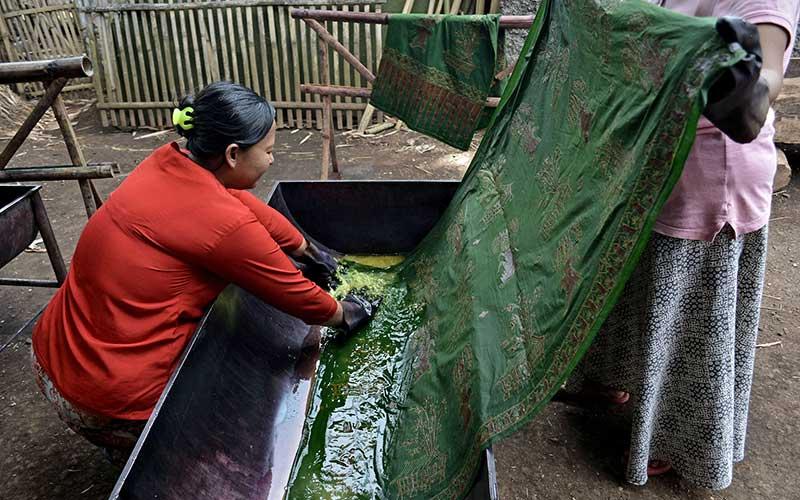 Perajin menyelesaikan proses pewarnaan batik tulis pasiran motif Leuit Pare di Samarang, Kabupaten Garut, Jawa Barat, Kamis (15/10/2020). Perajin kelompok batik Nirmala tersebut mempunyai ciri khas motif batik tulis seperti Leuit Pare, Mayang Kahuripan, Sampeu Antanan, dan Kembang Katresna yang dijual Rp.1 juta hingga Rp.1,5  juta tergantung tingkat kesulitan. ANTARA FOTO/Candra Yanuarsyah