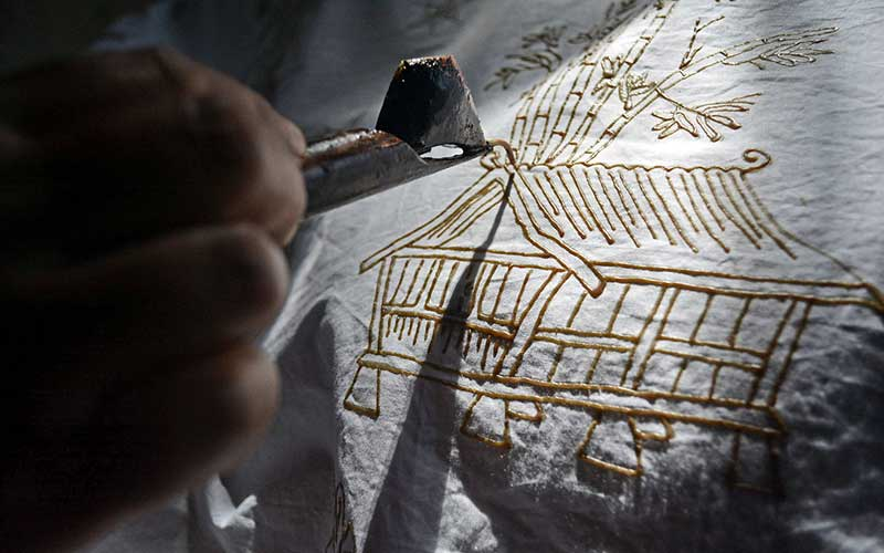 Perajin menyelesaikan pembuatan batik tulis pasiran motif Leuit Pare di Samarang, Kabupaten Garut, Jawa Barat, Kamis (15/10/2020). Perajin kelompok batik Nirmala tersebut mempunyai ciri khas motif batik tulis seperti Leuit Pare, Mayang Kahuripan, Sampeu Antanan, dan Kembang Katresna yang dijual Rp.1 juta hingga Rp.1,5  juta tergantung tingkat kesulitan. ANTARA FOTO/Candra Yanuarsyah