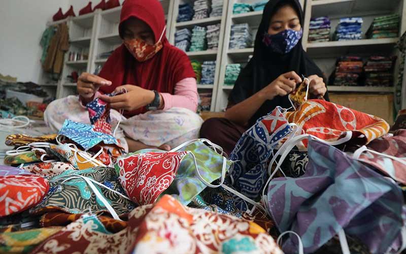 Pekerja membuat masker batik di tempat usaha batik bernama Batik Wistara di Surabaya, Jawa Timur, Sabtu (17/10/2020). Tempat produksi kain batik serta penjahitannya yang dijual dengan harga bervariatif itu memberdayakan 14 orang penyandang tunarungu dan tunawicara. ANTARA FOTO/Didik Suhartono