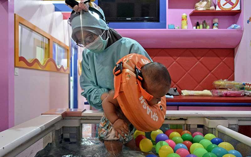 Seorang pemijat bayi mendampingi bayi berenang saat perawatan di Baby Spa Umay and Mom, Kota Garut, Kabupaten Garut, Jawa Barat, Sabtu (17/10/2020). Perawatan Baby Spa di tempat tersebut disiplin menerapkan protokol kesehatan secara ketat seperti penggunaan alat pelindung diri lengkap bagi pemijat dan pembagian masker medis secara gratis kepada pengunjung guna menghindari penularan Covid-19. ANTARA FOTO/Candra Yanuarsyah