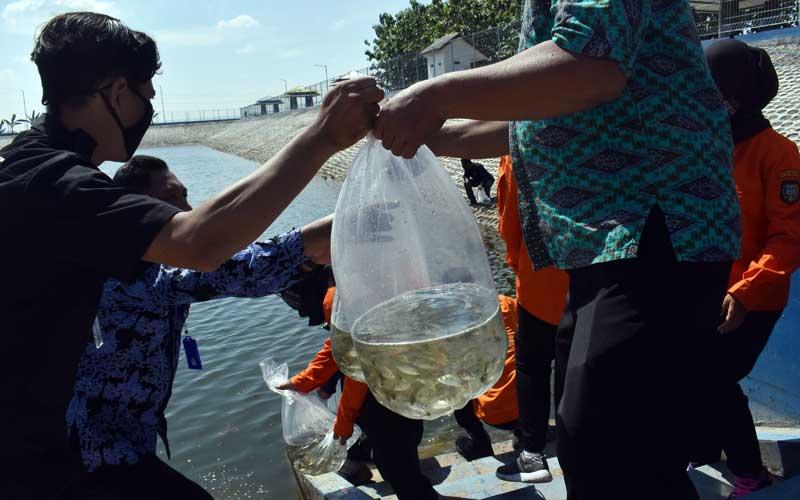 Petugas menebar benih ikan bantuan dari Pemprov Jawa Timur di Embung Pilangbango Kota Madiun, Jawa Timur, Selasa (20/10/2020). Pemprov Jawa Timur melalui Dinas Kelautan dan Perikanan memberikan bantuan 130 ribu benih ikan jenis lokal antara lain tawes, nila, tombro, wader cengkareng guna meningkatkan konsumsi ikan bagi masyarakat. ANTARA FOTO/Siswowidodo