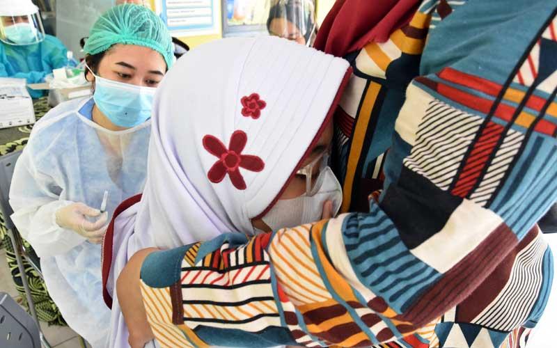 Seorang pelajar SD memeluk ibunya saat akan mendapatkan penyuntikan imunisasi oleh petugas Puskesmas di RPTRA Teratai, Tebet, Jakarta, Selasa (20/10/2020). Pemberian imunisasi Difteri Tetanus (DT) untuk mencegah penyakit infeksi seperti difteri tetanus bagi pelajar kelas satu dan imunisasi TD yang merupakan imunisasi lanjutan bagi pelajar kelas dua dan lima itu dilakukan dengan menumpang di RPTRA mengingat kegiatan di sekolah belum dibuka kembali di masa pandemi Covid-19. ANTARA FOTO/Indrianto Eko Suwarso
