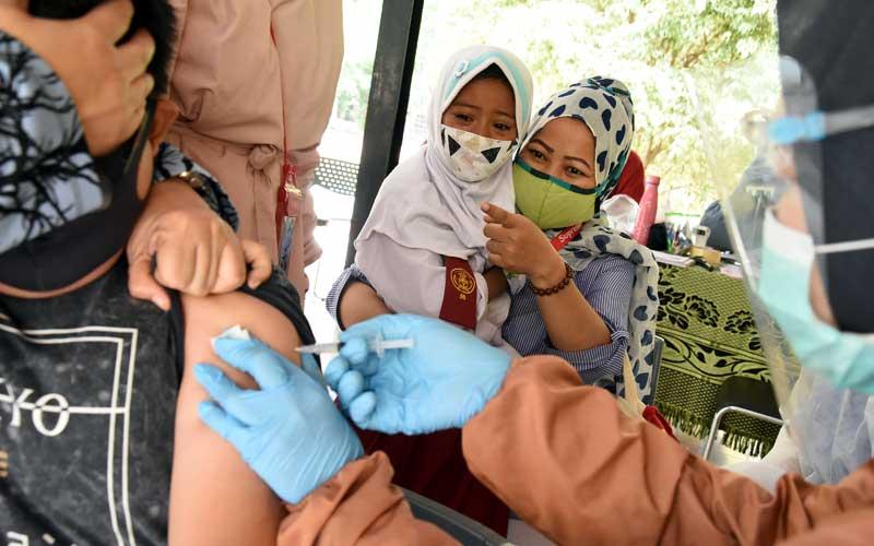 Seorang pelajar SD menangis saat akan mendapatkan suntikan imunisasi oleh petugas Puskesmas di RPTRA Teratai, Tebet, Jakarta, Selasa (20/10/2020). Pemberian imunisasi Difteri Tetanus (DT) untuk mencegah penyakit infeksi seperti difteri tetanus bagi pelajar kelas satu dan imunisasi TD yang merupakan imunisasi lanjutan bagi pelajar kelas dua dan lima itu dilakukan dengan menumpang di RPTRA mengingat kegiatan di sekolah belum dibuka kembali di masa pandemi Covid-19. ANTARA FOTO/Indrianto Eko Suwarso