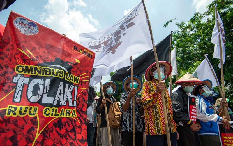 Sejumlah demonstran membawa poster dalam aksi jalan kaki menuju Istana Merdeka di Jalan Salemba, Jakarta, Selasa (20/10/2020). Aksi gabungan buruh, petani, mahasiswa, dan pelajar yang dilakukan bersamaan dengan setahun pemerintahan Presiden Joko Widodo dan Wakil Presiden Ma'ruf Amin itu menyuarakan penolakan pengesahan Undang-undang Cipta Kerja sekaligus meminta Presiden mengeluarkan Perppu pencabutan UU tersebut karena dinilai kurang berpihak pada rakyat kecil. ANTARA FOTO/Aditya Pradana Putra