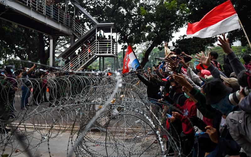 Massa aksi melakukan aksi unjuk rasa tolak UU Omnibus Law,  di kawasan Medan Merdeka Barat, Jakarta, Selasa (20/10/2020). Aksi gabungan buruh, petani, mahasiswa, dan pelajar yang dilakukan bersamaan dengan setahun pemerintahan Presiden Joko Widodo dan Wakil Presiden Ma'ruf Amin itu menyuarakan penolakan pengesahan Undang-undang Cipta Kerja sekaligus meminta Presiden mengeluarkan Perppu pencabutan UU. ANTARA FOTO/Galih Pradipta