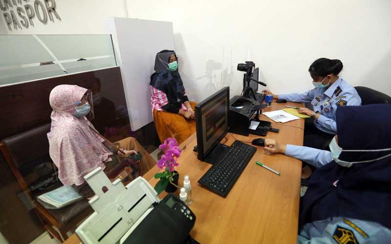 Petugas melayani warga yang membuat paspor di Unit Layanan Paspor di Mal WTC Matahari Serpong, Tangerang Selatan, Selasa (20/10/2020). Bisnis