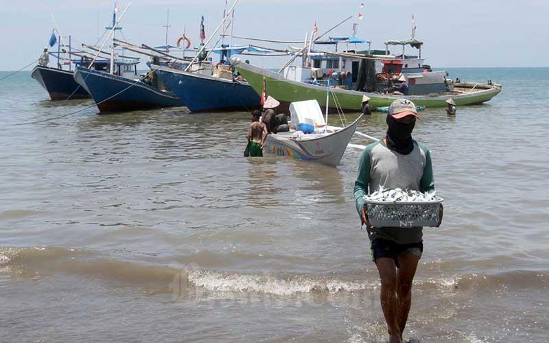 Buru memindahkan ikan dari kapal dipelelangan ikan Beba, Galesong Utara Kabupaten Takalar, Sulawesi Selatan, Rabu (21/20/2020). Kementerian Kelautan dan Perikanan (KKP) menyusun daftar penyakit ikan berbahaya sebagai salah satu upaya guna menjaga dan memastikan kontinuitas pasokan komoditas perikanan berkualitas ekspor dari Indonesia. Bisnis/Paulus Tandi Bonern