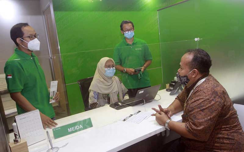 Head of Sharia Business Development and Strategy Harsa Martana (kiri) dan Direktur & Chief of Employee Benefits dan Syariah Manulife Indonesia Karjadi Pranoto (kedua kanan) melayani nasabah di sela-sela peluncuran MiSmart Insurance Solution (Mission) Syariah di Jakarta, Kamis (22/10/2020). Bisnis/Himawan L Nugraha