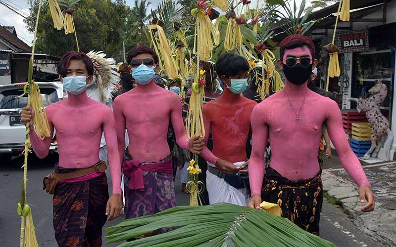 Sejumlah warga yang tubuhnya dihias warna-warni dan menggunakan masker saat berkeliling kampung dalam tradisi Ngerebeg di Desa Tegallalang, Gianyar, Bali, Kamis (22/10/2020). Tradisi yang merupakan ritual tolak bala tersebut biasanya diikuti ratusan warga, namun tahun ini digelar dengan jumlah terbatas sekitar 36 orang dengan menerapkan protokol kesehatan Covid-19. ANTARA FOTO/Nyoman Hendra Wibowo