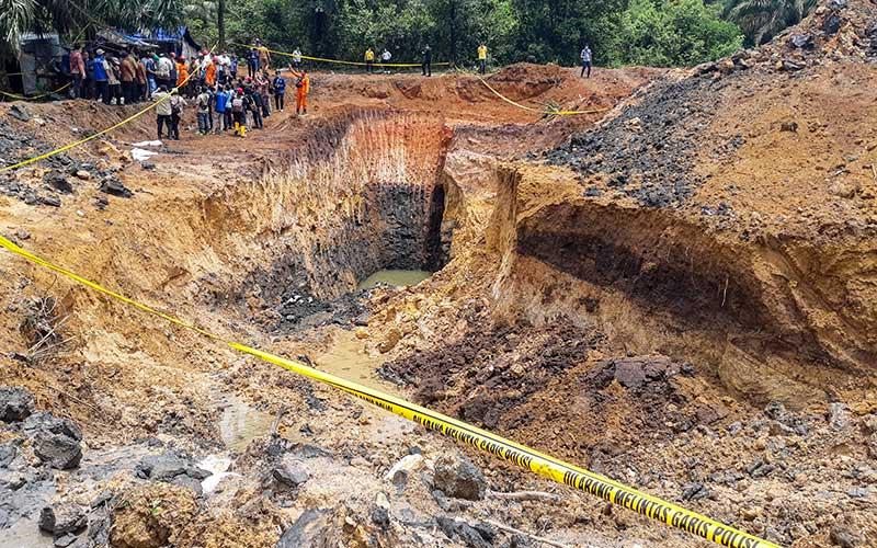Warga mengamati lokasi tambang batu bara ilegal yang mengalami longsor di Desa Tanjung Lalang, Kecamatan Tanjung Agung, Kabupaten Muara Enim, Kamis (22/10/2020).  Sebanyak 11 orang pekerja tambang batu bara ilegal meninggal dunia akibat tertimbun longsor pada Rabu (21/10). ANTARA FOTO/Sabang Dipa