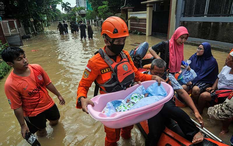 Petugas Badan Penanggulangan Bencana Daerah (BPBD) mengevakuasi anak bayi saat banjir di Jatirasa, Bekasi, Jawa Barat, Minggu (25/10/2020). Banjir akibat luapan kali Cikeas memasuki permukiman pada (24/10) pukul 23.00 WIB dan merendam ratusan rumah warga. ANTARA FOTO/ Fakhri Hermansyah
