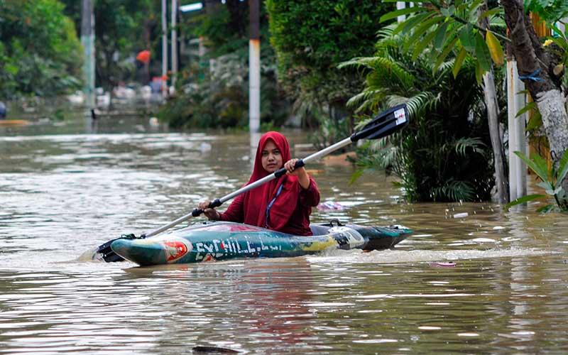 Seorang warga menggunakan perahu kano saat banjir di Jatirasa, Bekasi, Jawa Barat, Minggu (25/10/2020). Banjir akibat luapan kali Cikeas memasuki permukiman pada (24/10) pukul 23.00 WIB dan merendam ratusan rumah warga. ANTARA FOTO/ Fakhri Hermansyah