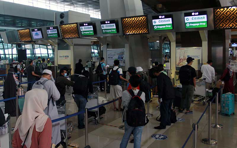 "Calon penumpang antre untuk ""check in"",   di Terminal 3 Bandara Soekarno Hatta, Tangerang, Banten, Senin (26/10/2020). Kementerian Perhubungan memprediksi kenaikan pergerakan penumpang pesawat mencapai 20 persen di masa libur panjang 28 Oktober hingga 1 November 2020 dengan adanya subsidi harga tiket pesawat yang diberikan pemerintah. ANTARA FOTO/Muhammad Iqbal"