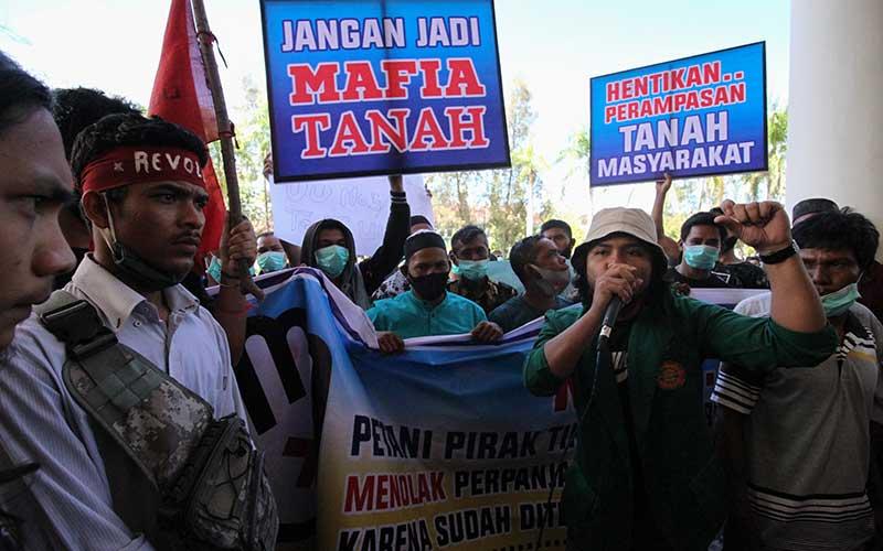 Massa dari aliansi Masyarakat Petani Agraris dan Liga Mahasiswa Nasional untuk Demokrasi membawa alat peraga saat aksi unjuk rasa di halaman kantor bupati Aceh Utara, Aceh, Kamis (19/11/2020). Mereka mendesak segera hentikan perpanjangan izin 551 haktar tanah eks HGU yang ditelantarkan sejak 1998 dan menuntut pemerintah mengeluarkan sertifikat kepada masyarakat melalui program Tanah Objek Reforma Agraria (TORA) yang dicanangkan Presiden Joko Widodo. ANTARA FOTO/Rahmad