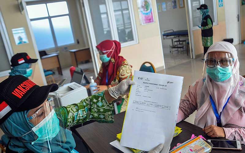 Petugas medis memberikan surat vaksinasi Covid-19 kepada warga saat simulasi di Puskesmas Cikarang, Kabupaten Bekasi, Jawa Barat, Kamis (19/11/2020). Simulasi vaksinasi Covid-19 tersebut merupakan bagian dari upaya pemerintah menyampaikan sosialisasi tentang vaksin Covid-19 yang saat ini masih dalam tahap uji klinis. ANTARA FOTO/Fakhri Hermansyah