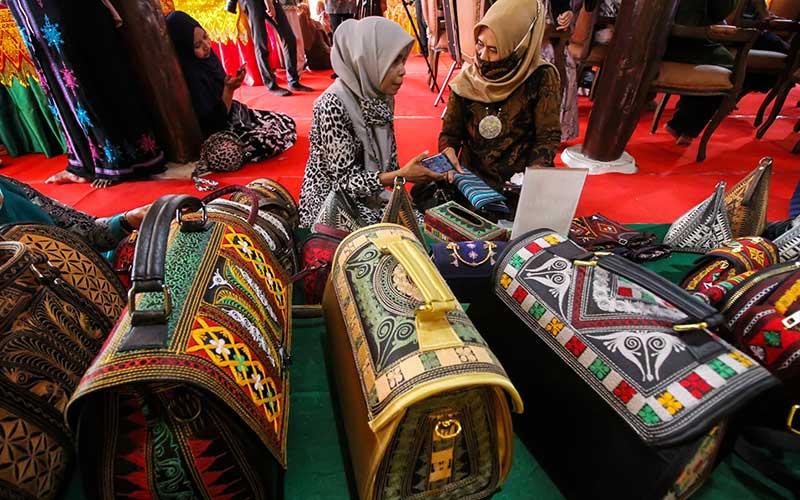 """Pelaku Usaha Mikro Kecil Menengah (UMKM) menata tas motif Aceh pada Pameran UMKM Kreatif Bank Indonesia (BI) di komplek Museum Lhokseumawe, Aceh, Sabtu (21/11/2020). Pameran bertemakan """"UMKM Sahabat Milenial"""" itu, upaya BI mendukung peningkatan kontribusi UMKM dalam perekonomian nasional sekaligus mendorong generasi muda cinta produk lokal dan nasional dengan memamfaatkan platform digital (marketplace). ANTARA FOTO/Rahmad"""