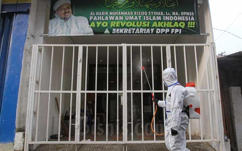 Petugas menyemprotkan cairan disinfektan di Jalan Petamburan III, Jakarta, Minggu (22/11/2020). Jajaran Polda Metro Jaya melakukan disinfekta di area markas Front Pembela Islam (FPI) dan sekitarnya untuk menekan penularan Covid-19. Bisnis/Arief Hermawan P