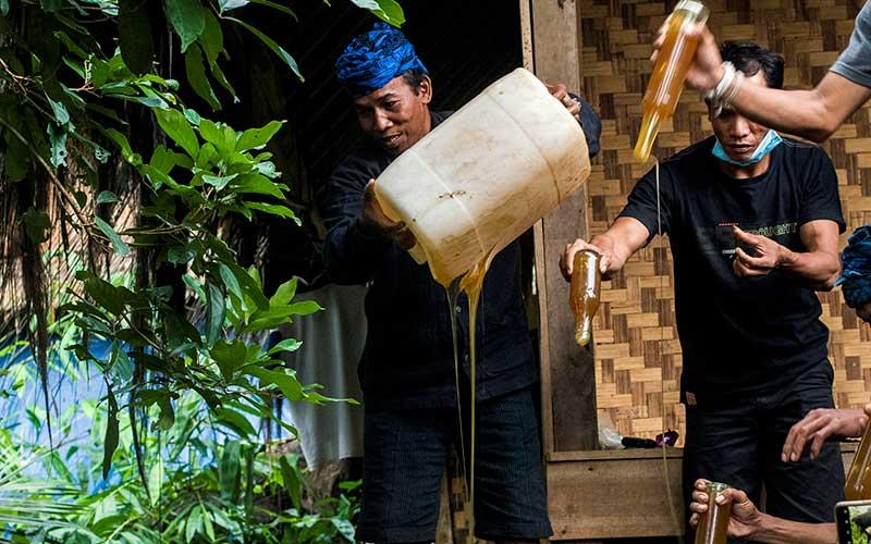 Warga Baduy membuang barang bukti madu palsu sitaan dari masyarakat Baduy di Kampung Kaduketug, Lebak, Banten, Minggu (22/11/2020). Lembaga adat Baduy memusnahkan sebanyak 20 botol dan satu jerigen isi 40 liter madu palsu yang beredar di kalangan masyarakat Baduy setempat. ANTARA FOTO/Muhammad Bagus Khoirunas