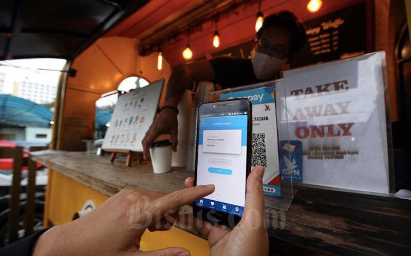 Konsumen melakukan transaksi pembayaran menggunakan aplikasi uang elektronik BJB DigiCash di salah satu kedai kopi di Bandung, Jawa Barat, Selasa (24/11/2020). Proses transformasi digitalisasi layanan perbankan sedang gencar-gencarnya dilakukan PT Bank Pembangunan Daerah Jawa Barat dan Banten, Tbk. (Bank BJB). Bisnis/Rachman