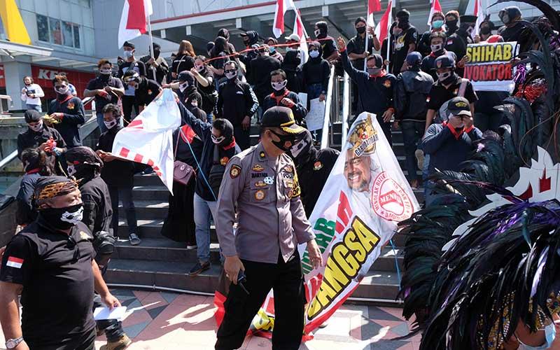 Personel polisi meminta massa membubarkan diri saat aksi damai Menjaga Persatuan dan Kesatuan Bangsa di Mertoyudan, Magelang, Jateng, Sabtu (23/11/2020). Jajaran Polres Magelang terpaksa membubarkan aksi damai oleh ratusan warga tersebut karena menimbulkan kerumunan massa yang berpotensi menyebarkan Covid-19. ANTARA FOTO/Anis Efizudin