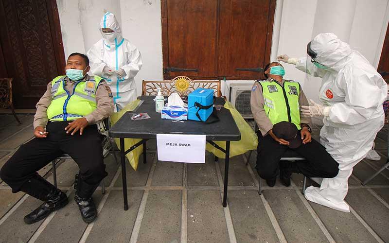 Sejumlah polisi mengikuti tes usap di Polrestabes Surabaya, Jawa Timur, Sabtu (28/11/2020). Sekitar 1.131 anggota kepolisian yang akan bertugas melaksanakan pengamanan di Tempat Pemungutan Suara (TPS) pada Pilkada Surabaya 2020 tersebut mengikuti tes usap sebagai upaya untuk mencegah penyebaran Covid-19. ANTARA FOTO/Didik Suhartono