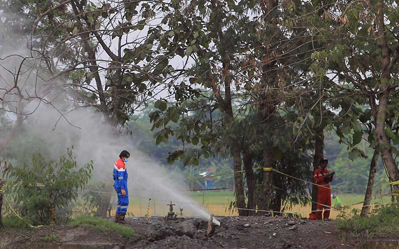 Pekerja  Pertamina EP memeriksa semburan gas liar di desa Sukaperna, Tukdana, Indramayu, Jawa Barat, Senin (30/11/2020). Semburan gas liar bercampur air dan lumpur yang sudah terjadi sejak beberapa minggu lalu itu diduga bersumber dari sumur peninggalan Belanda yang sudah tidak digunakan. ANTARA FOTO/Dedhez Anggara