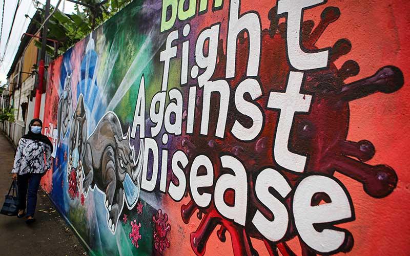 Seorang warga melintas di depan mural tentang Covid-19 di Pinang, Kota Tangerang, Banten, Senin (30/11/2020). Satgas Penanganan Covid-19 mencatat Provinsi Banten masuk ke dalam lima besar provinsi yang mencatatkan kenaikan jumlah kasus tertinggi pada Senin (30/11/2020) yakni sebesar 262 kasus sehingga totalnya menjadi 13.061, sedangkan kasus pasien sembuh sebanyak 145 orang dengan total kasus sembuh menjadi 8.912 orang. ANTARA FOTO/Fauzan