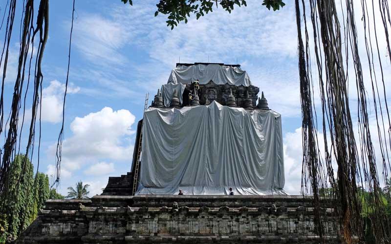 Pekerja mamasang terpaulin untuk penutupan Candi Mendut di Mungkid, Magelang, Jawa Tengah, Selasa (1/12/2020). Balai Konservasi Borobudur (BKB) menutup tiga candi yaitu Borobudur, Mendut dan Pawon sebagai langkah antisipasi melindungi batu candi dari abu vulkanik jika terjadi erupsi Gunung Merapi. ANTARA FOTO/Anis Efizudin