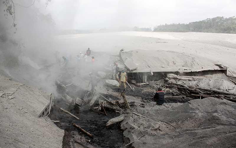 Warga melihat alat berat yang terkubur akibat lahar panas erupsi Gunung Semeru di kawasan Besuk Kobokan, Pronojiwo, Lumajang, Jawa Timur, Rabu (2/12/2020). Banjir lahar panas Gunung Semeru tersebut mengakibatkan terputusnya akses jalan antarkecamatan di Lumajang serta sejumlah truk dan alat berat penambang pasir terkubur material lahar panas. ANTARA FOTO/Umarul Faruq