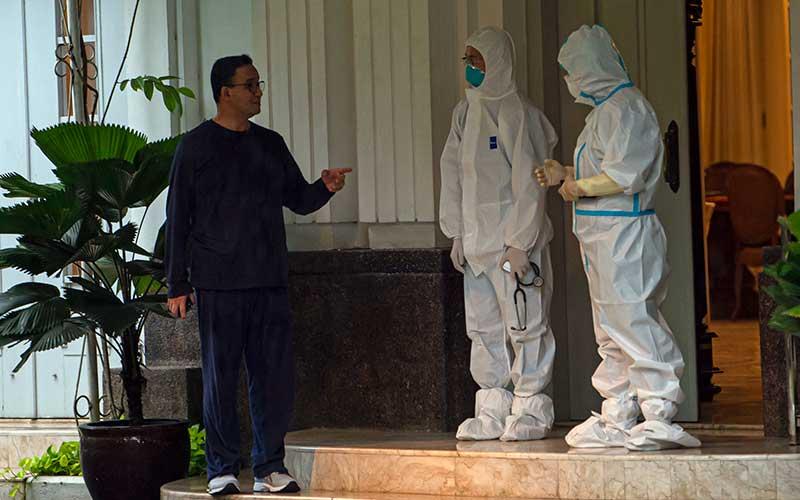 Gubernur DKI Jakarta Anies Baswedan berbicara dengan tim medis yang menanganinya saat menjalani isolasi di rumah dinasnya di Menteng, Jakarta Pusat, Kamis (3/12/2020). Anies Baswedan terkonfirmasi positif Covid-19 sejak Selasa (1/12) setelah melakukan tes usap PCR pada Senin (30/11) dan saat ini menjalani isolasi mandiri tanpa didampingi keluarga. ANTARA FOTO/Aditya Pradana Putra