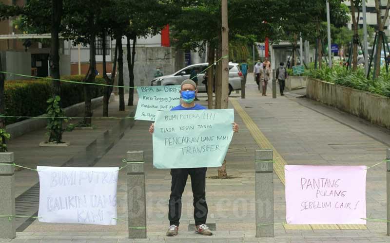 Nasabah memegang poster tuntutan saat unjuk rasa di halaman kantor AJB Bumiputera 1912 di Jakarta, Kamis (3/12/2020). Nasabah korban gagal bayar Asuransi Jiwa Bersama (AJB) Bumiputera 1912 menggelar unjuk rasa guna menuntut pencairan klaim kepada perusahaan. Seperti diketahui, Bumiputera memiliki sekitar 4-5 juta pemegang polis dengan sekitar 365.000 polis yang telah jatuh tempo serta total tunggakan mencapai Rp10 triliun. Bisnis/Himawan L Nugraha