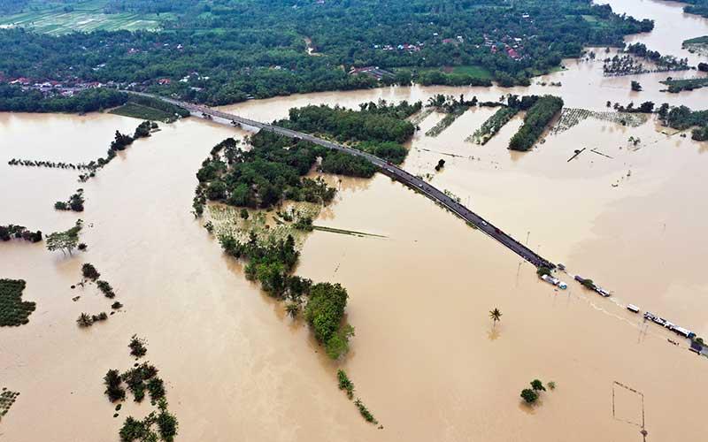 Foto udara banjir dari luapan Kali Klawing menggenangi jalur penghubung Kabupaten Banyumas-Purbalingga di Jembatan Linggamas, Desa Petir, Kalibagor, Banyumas, Jawa Tengah, Kamis (3/12/2020). Curah hujan ekstrim pada Rabu (2/12) malam di wilayah selatan Jawa Tengah menyebabkan sejumlah sungai di Kabupaten Banyumas dan Purbalingga meluap sehingga menyebabkan beberapa titik jalan dan permukiman warga terendam banjir. ANTARAFOTO/Idhad Zakaria