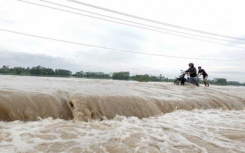 Dua orang warga menerobos banjir luapan Kali Klawing yang merendam jalur penghubung Kabupaten Banyumas-Purbalingga di Jembatan Linggamas, Desa Petir, Kalibagor, Banyumas, Jawa Tengah, Kamis (3/12/2020). Curah hujan ekstrim pada Rabu (2/12) malam di wilayah selatan Jawa Tengah menyebabkan sejumlah sungai di Kabupaten Banyumas dan Purbalingga meluap sehingga menyebabkan beberapa titik jalan dan permukiman warga terendam banjir. ANTARAFOTO/Idhad Zakaria